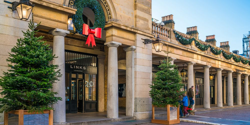 LONDON DECEMBER 28, 2017: Tourists and Londoners enjoy sunny day in Covent Garden, one of the most popular  shopping and tourist sites in London known for its restaurants, shops and live entertainment